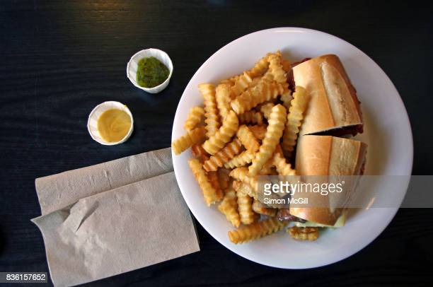 Cheese steak sandwich with crinkle cut potato chips on a white plate at a diner in New York City, United States of America