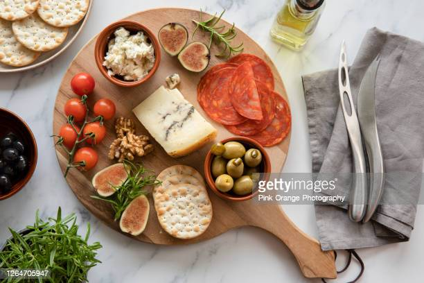 kaas, tomaten, chorizo, crackers, olijven op een ronde houten plank, schotel. - kaasplank stockfoto's en -beelden