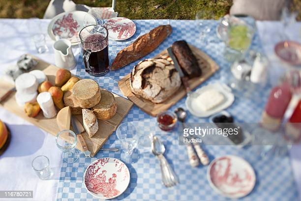 cheese wheels, bread and a lot of crockery on a dining table outside
