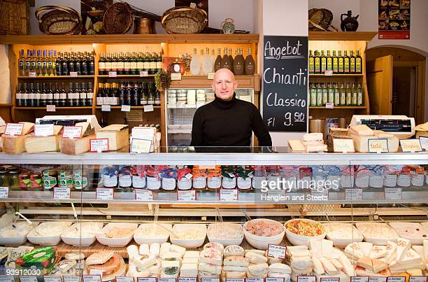 cheese, wine store owner in shop - delicatessen stock photos and pictures