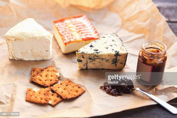 Cheese with crackers and preserves on table