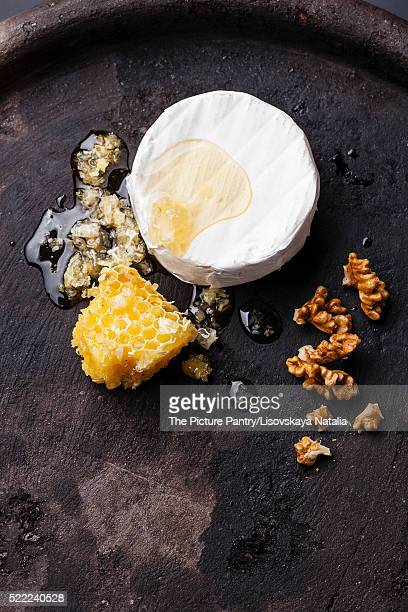 Cheese with honey and nuts on black textured background