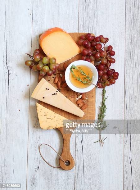 A cheeseboard with grapes, almond olive oil and rosemary