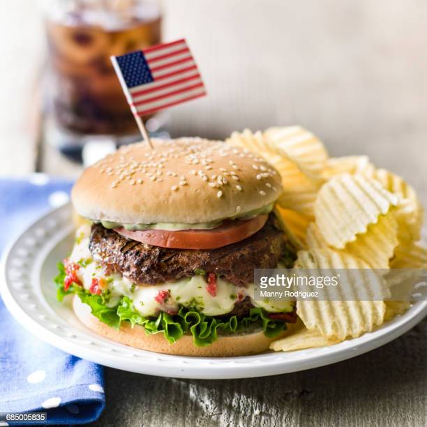 Cheeseburger and potato chips with American flag