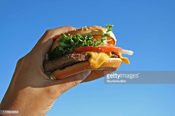 Cheeseburger in a left hand about to be eaten