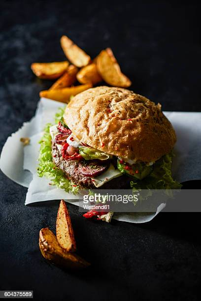 Cheeseburger on greaseproof paper and potato wedges