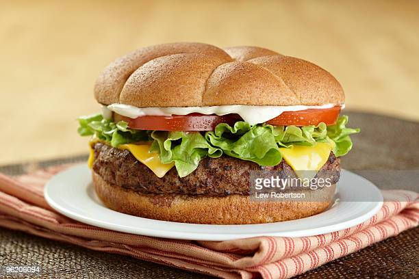 cheeseburger on plate with napkin - three objects stock pictures, royalty-free photos & images