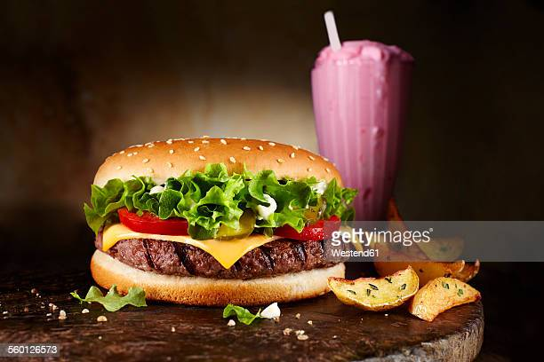 Cheeseburger, strawberry milkshake and potatoe wedges