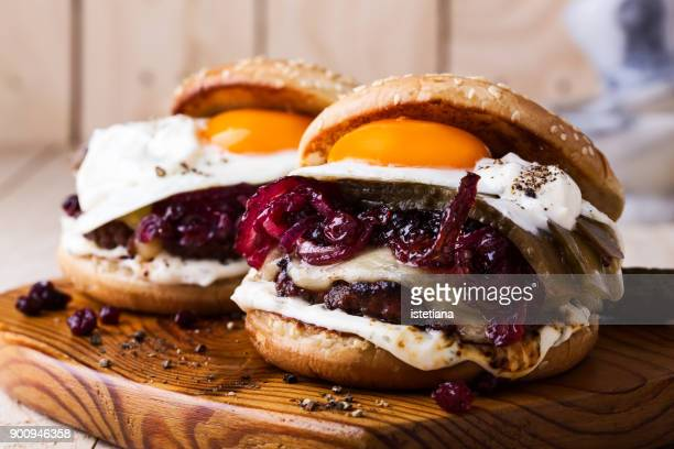 cheeseburger with caramelized onions, fried egg and aioli - juicy stock pictures, royalty-free photos & images