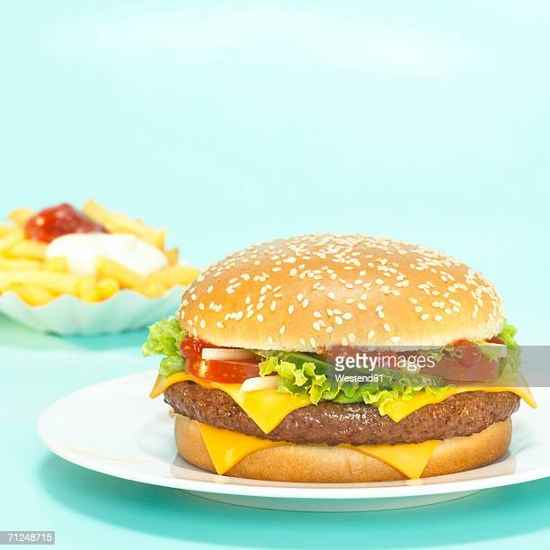 Cheeseburger with French fries, focus on hamburger, close-up