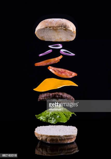 cheeseburger with ingredients mid-air - hamburger stock pictures, royalty-free photos & images