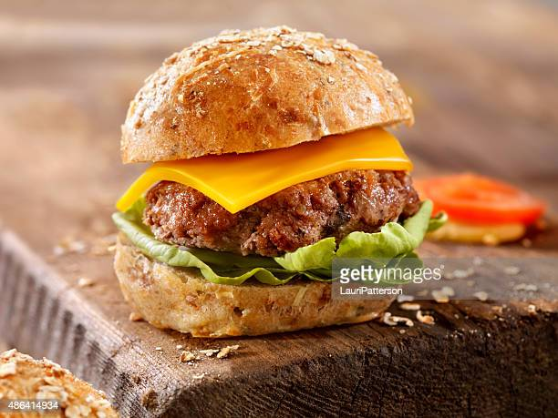 cheeseburgeron a rustic wood cutting board - cheeseburger stock pictures, royalty-free photos & images