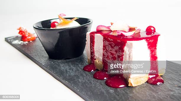 Cheesecake And Ice Cream Served In Plate Over White Background