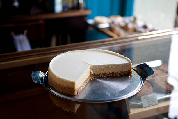 a cheesecake cut into slices on a display cabinet in a coffee shop - 芝士蛋糕 個照片及圖片檔