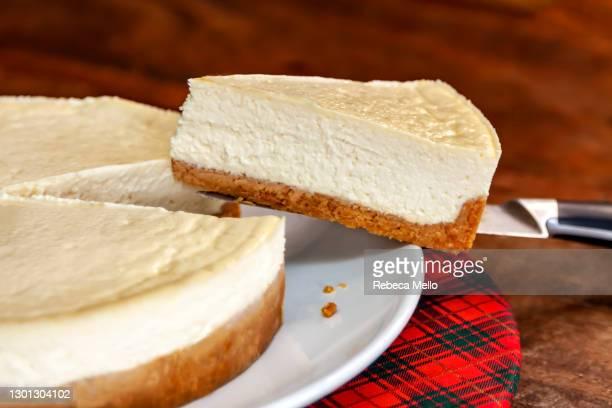 cheesecake slice on a knife - チーズケーキ ストックフォトと画像