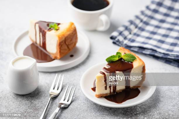 cheesecake with chocolate sauce and cup of coffee - cheesecake stock pictures, royalty-free photos & images