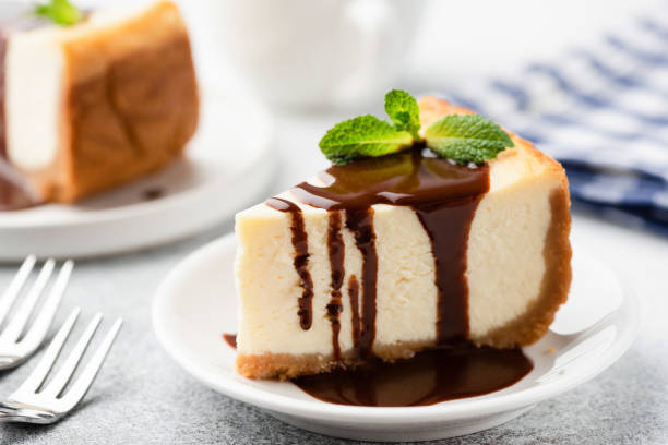 cheesecake with chocolate sauce on plate - 芝士蛋糕 個照片及圖片檔