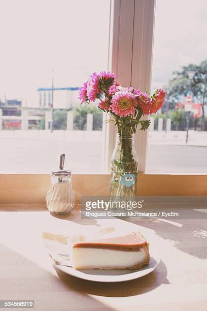 Cheesecake With Flower In Bottle On Window Sill