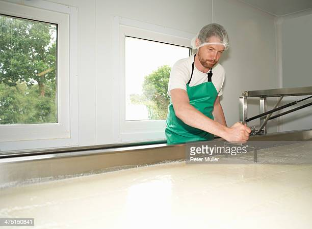 Cheesemaker slicing through curds at farm factory