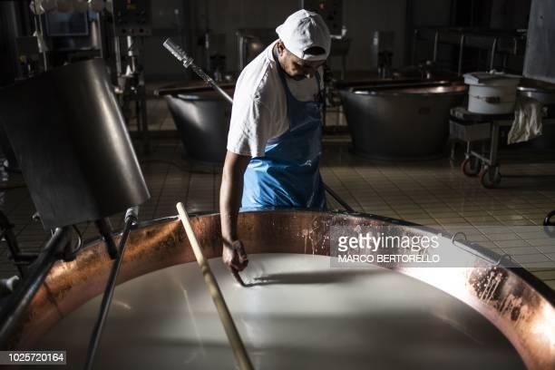 A cheesemaker works at a Parmigiano Reggiano factory in the Dall'Aglio Farm on September 1 2018 in Gattatico near Reggio Emilia Cheesemaker Singh...