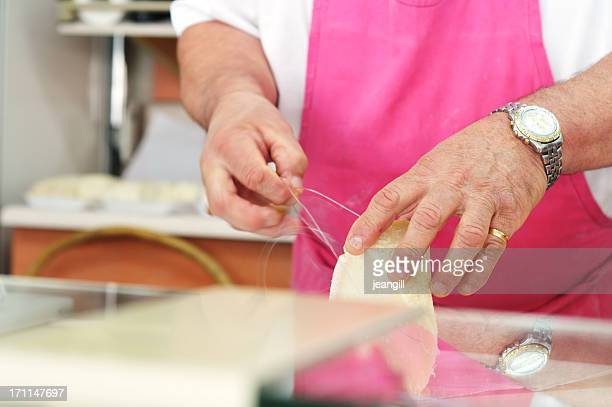 cheesemonger cutting parmesan with wire