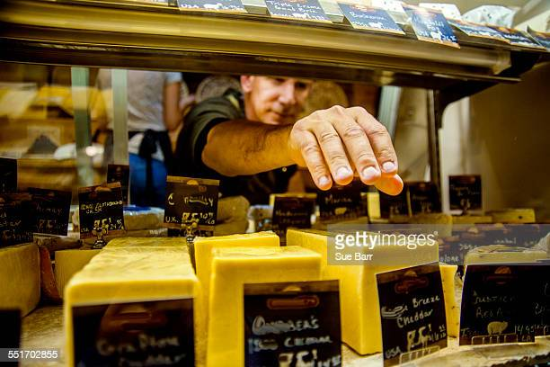 cheesemonger reaching for cheese in display - delicatessen stock pictures, royalty-free photos & images