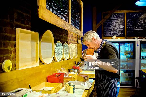 Cheesemonger smelling cheese