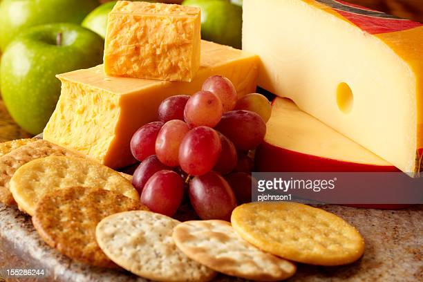 Cheeses and crackers with apples and grapes