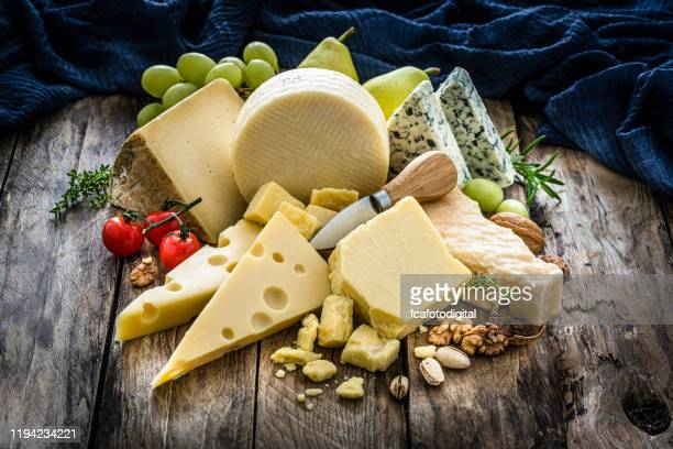 cheeses selection on rustic wooden table - cheese stock pictures, royalty-free photos & images