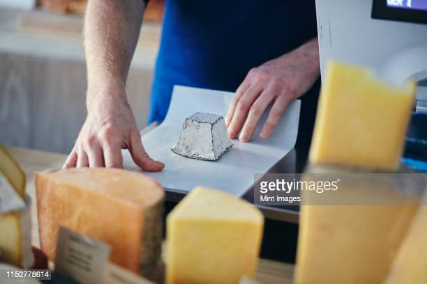 cheeseseller wrapping up goats cheese - delicatessen stock pictures, royalty-free photos & images