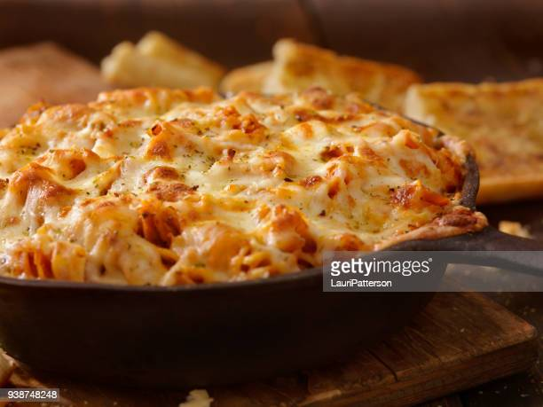 cheesy baked rotini pasta in roasted tomato and garlic sauce with garlic bread - cheese stock photos and pictures