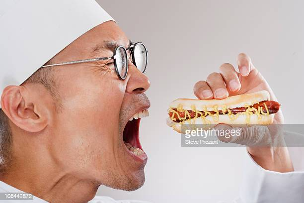 Chef about to eat a hotdog