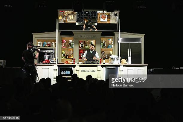 Chef Adam Richman gives a cooking demonstration on stage at the Grand Tasting presented by ShopRite featuring KitchenAid® culinary demonstrations...