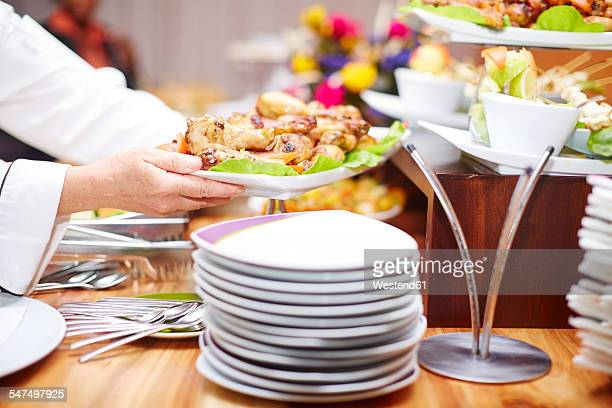 Chef adding chicken pieces to buffet