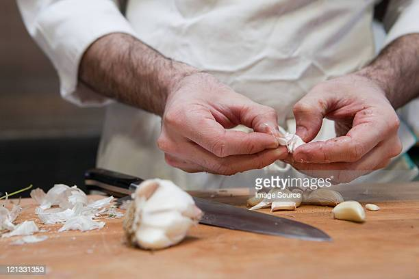 Chef adding peeling garlic