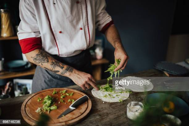 Chef adds salad on tortilla
