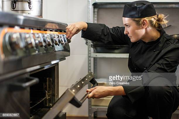 Chef adjusting temperature of oven in kitchen