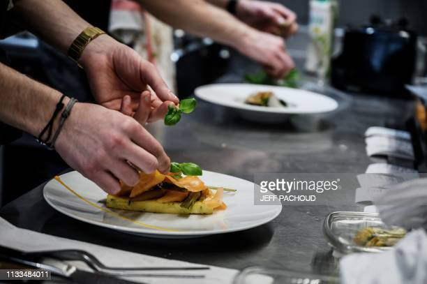 Chef Adrien Zedda prepares a dish in the kitchen of his culinary gourmet vegetarian restaurant Culina Hortus in Lyon on March 26, 2019. - Quality...