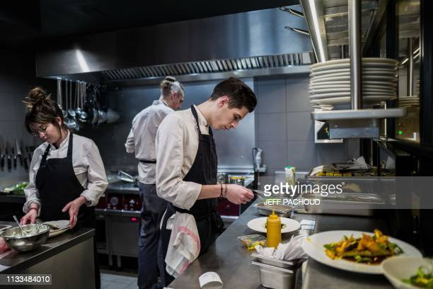 Chef Adrien Zedda works in the kitchen of his culinary gourmet vegetarian restaurant Culina Hortus in Lyon on March 26, 2019. - Quality wines,...