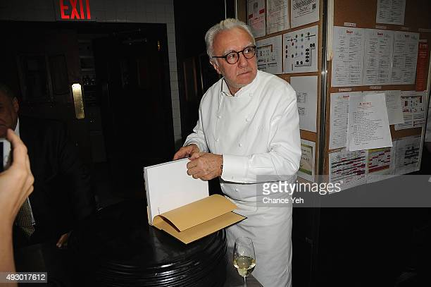 Chef Alain Ducasse signs a book at An Evening With Alain Ducasse And Friends part of the Bank Of America Dinner Series during Food Network Cooking...