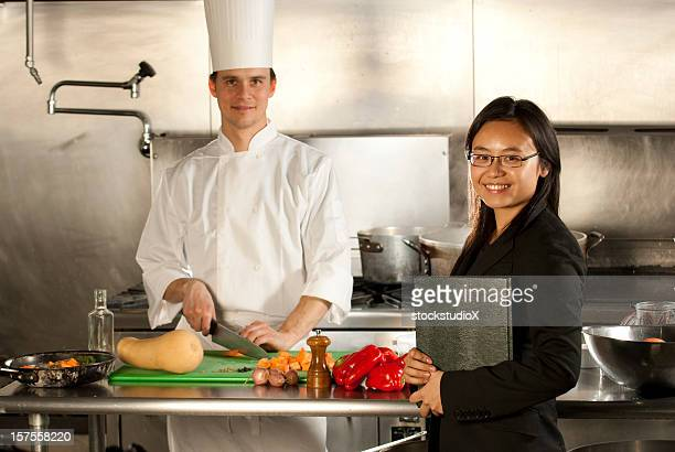 A chef and a waitress in the kitchen