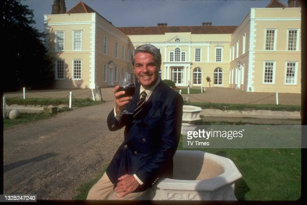 Chef and cookery writer Robert Carrier with a glass of wine outside his restaurant at Hintlesham Hall in Suffolk, circa 1980.