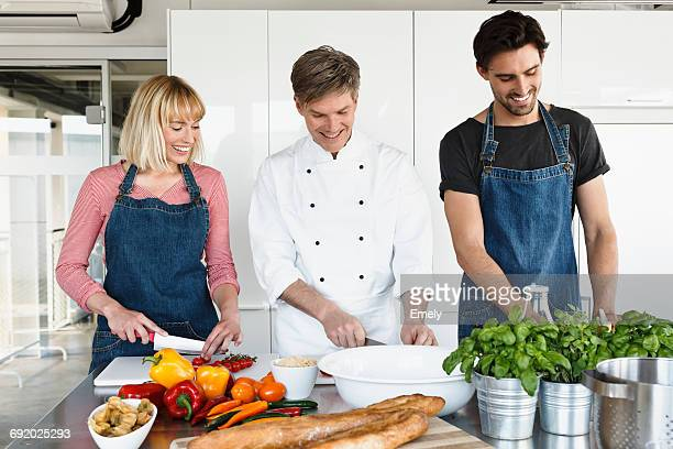 Chef and couple in kitchen slicing vegetables