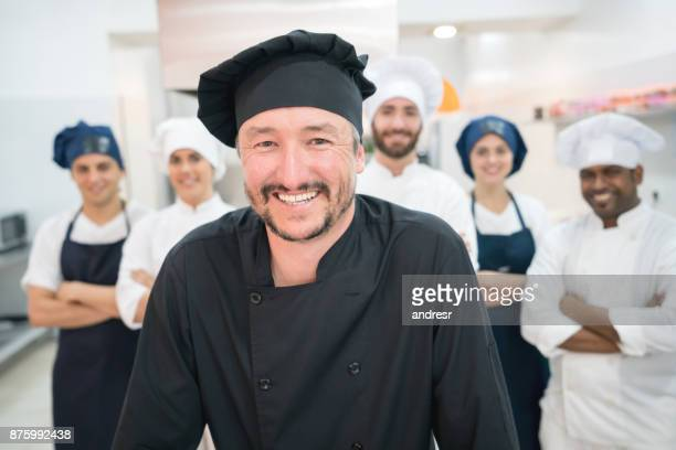 Chef and his multi ethnic team at the kitchen looking at camera smiling