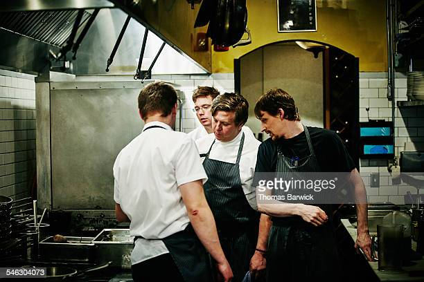 Chef and kitchen staff discussing food preparation