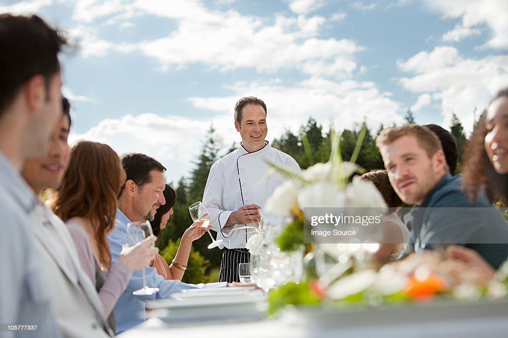 Chef and people at outdoor dinner party : Stock Photo