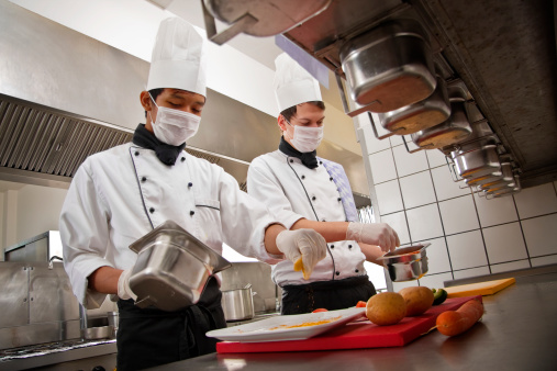Chef and trainee work in a hotel kitchen, preparing a meal 186885086