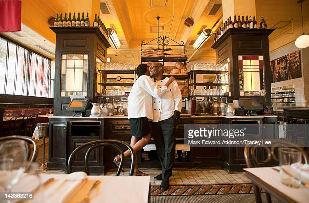 Chef and waitress hugging in restaurant