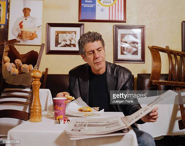 Chef Anthony Bourdain is photographed eating a sandwich and reading a newspaper in June 2003 at Brasserie Les Halles on Park Avenue in New York City