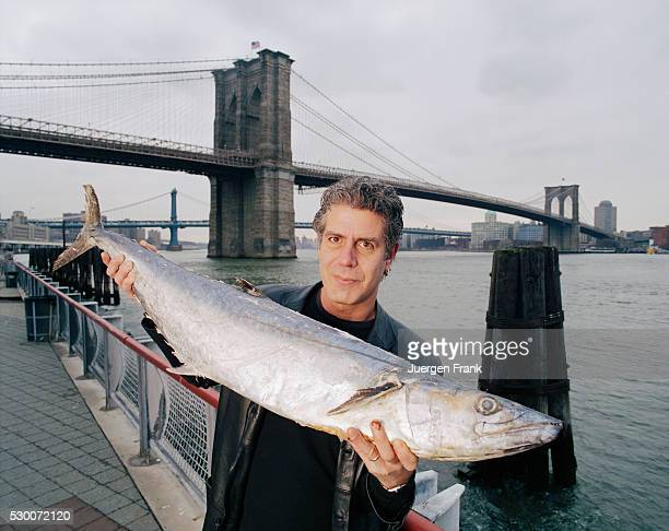 Chef Anthony Bourdain is photographed in June 2003 holding up a mackerel at the Fulton Fish Marketin New York City